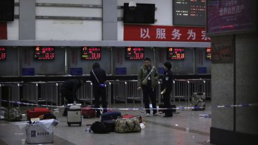 Police stand near luggage left at the ticket office after a group of armed men attacked people at Kunming railway station, Yunnan province.