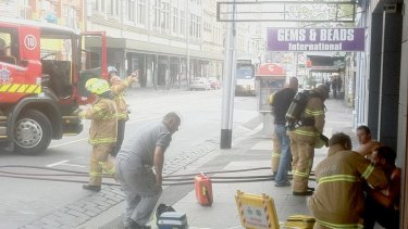 Firefighters treat two men at the scene of the explosion.