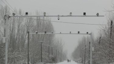 Big brother: Surveillance cameras keep watch on the roads entering Pilal village in Xinjiang.