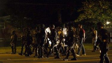 Police officers patrol a street in Ferguson, Missouri.