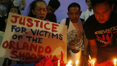 Filipinos light candles during a vigil to pay tribute to the victims of the Orlando, Fla. mass shooting.