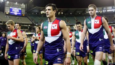 A dejected Dockers captain, Matthew Pavlich, leads his teammates off the ground after they were thrashed by the Cats.