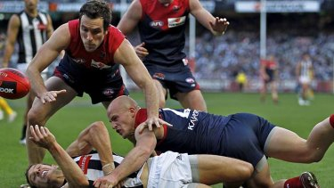 Dropping the Ball: Demon Nathan Jones dumps Magpie Luke Ball as Joel Macdonald is poised to pounce on the crumbs.