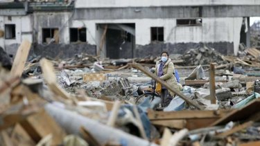 A masked woman yesterday wheels a bicycle and searches the debris from the March 11 earthquake and tsunami in Rikuzentakata in Iwate prefecture on the north-east of Japan's Honshu island.