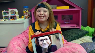 Little girl with a big impact: Sophie Deane holds up a photo of Julia Gillard.