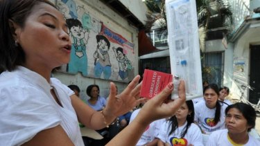 A Philippine health worker holds samples of contraceptives during a lecture to women in 2011.