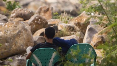 Illicit tryst ... a couple cuddle at the Ulele beachfront despite the attentions of local police.