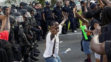 A man attempts to stop protesters from engaging with police in riot gear in front of the Baton Rouge Police Department headquarters.
