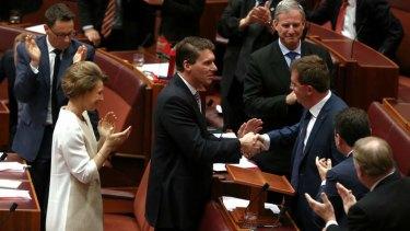 Senator James McGrath is congratulated by Senator Cory Bernardi after delivering his first speech. Photo: Alex Ellinghausen