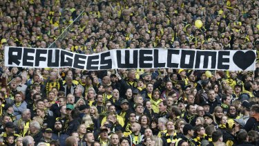Soccer fans in Dortmund supporting Germany's open door stance: Europe's largest economy may benefit from the influx of refugees.