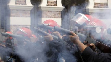 Malaysian riot police officers fire tear gas during a rally calling for electoral reforms in Kuala Lumpur.