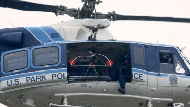 A US Park Police helicopter flies over a building at the Washington Navy Yard.