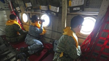 Military personnel look out of a Singapore Air Force plane during the search.