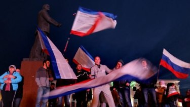 People wave Russian flags in Lenin Square in Simferopol to celebrate the preliminary results of the Crimean referendum.