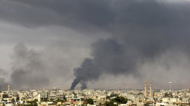 Smoke rises over Benghazi after clashes between militants, former rebel fighters and government forces.