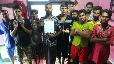 Bangladeshi asylum seekers back in their home in Cisarua, West Java, after being held on Australian ships for five days then send back on an Australian life-boat. Some hold the papers given to them by Customs officers, others hold the wrist bands they wore on the Australian ships.