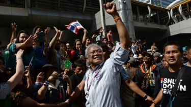 Thai protest leader Suthep Thaugsuban (C) raises his fist as anti-government protesters march in downtown Bangkok as part of their ongoing rallies.