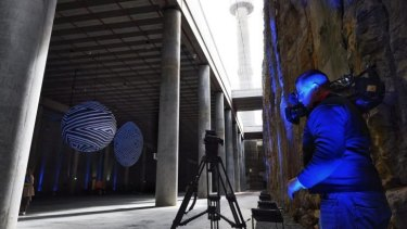 A cameraman taking shots of Andrew's work displayed in the huge space at Barangaroo .
