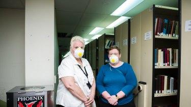 Senior archivist Sarah Lethbridge and university librarian Roxanne Missingham survey the damage after last weekend's floods.