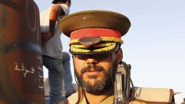 Changing of the guard … a rebel poses in one of Gaddafi's caps.