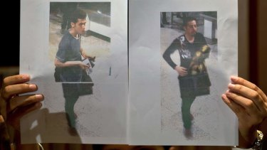A Malaysian police official displays photographs of the two men who boarded the Malaysia Airlines flight using stolen passports. The man on the left has been identified as Pouria Nour Mohammad Mehrdad, a 19-year-old Iranian asylum seeker. The man on the right is yet to be identified.