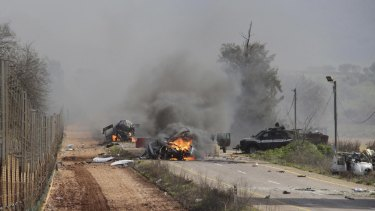 Burning vehicles are seen near the village of Ghajar on Israel's border with Lebanon. A Hezbollah missile strike killed two and wounded seven Israeli soldiers on Wednesday.