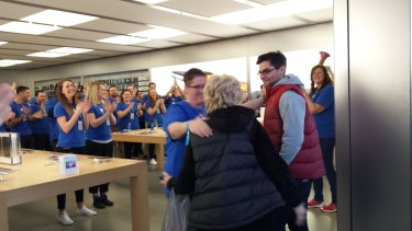 David Brown, first in line at Chadstone, gets a hug from Apple staff as doors opened.