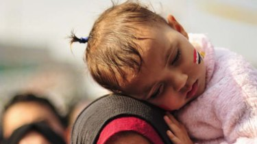 A girl with an Egyptian flag painted on her face sleeps on her mother's shoulder during a demonstration in Tahrir Square.