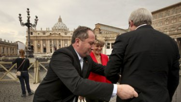 The hem of his garment ... Julie Bishop watches as Barnaby Joyce straightens Kevin Rudd's coat in Rome.
