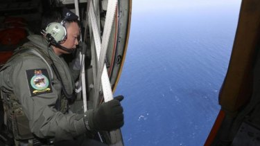 A member of the military personnel looks out of a Republic of Singapore Air Force C-130 transport plane during the search for the missing Malaysia Airlines MH370 plane over the South China Sea.