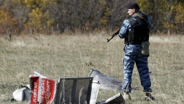 A policeman representing Donetsk People's Republic stands guard at the crash site of the downed Malaysia Airlines flight MH17, near the village of Grabovo.