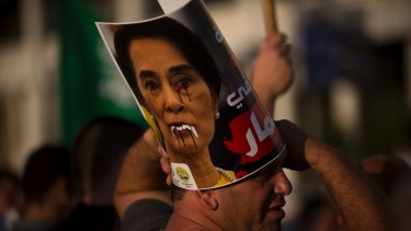 A member of the Islamic Movement in Israel holds a defaced poster of  Aung San Suu Kyi during a demonstration in Tel Aviv.