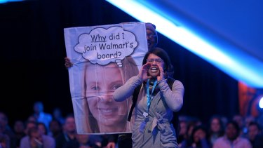 A protester shouts as Yahoo CEO Marissa Mayer speaks in conversation with Salesforce chairman and CEO Marc Benioff at the 2013 Dreamforce conference in San Francisco.