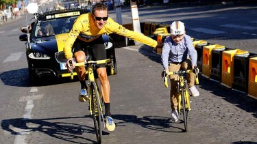 Father and son ... Tour de France winner Bradley Wiggins parades through Paris with his son, Ben.