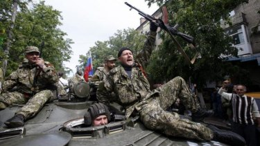 Pro-Russian gunmen atop an armored personal carrier shout slogans during a Victory Day celebration, which commemorates the 1945 defeat of Nazi Germany, in Slovyansk, eastern Ukraine.