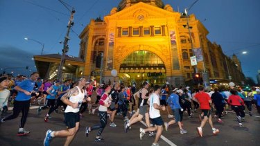 Runners pass Flinders Street Station in the early hours of the morning.