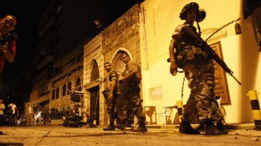 Street warfare ... Lebanese soldiers patrol outside a mosque in Beirut after fighting broke out between  Hezbollah and a Sunni group.