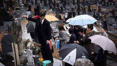 Kenji Sasaki, 44 pours water over the gravesite of five family members, his 100-year-old grandfather, mother, father, eldest sister and 17-year-old niece who were all killed when their home was swept away by the tsunami one year ago in Rikuzentakata, Japan.