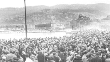 Crowds wait for a ship on the dockside at Trieste.
