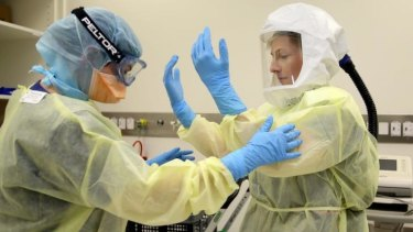 Royal Melbourne Hospital staff demonstrate personal protection equipment.