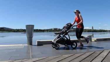 Enjoying the sunshine ... lunchtime jogger Melissa Eagles with her 13 month old son, Finn, hitching a ride.