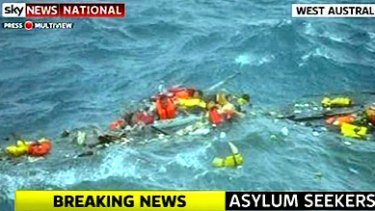 Asylum seekers struggle to cling to wreckage in huge seas off Christmas Island.