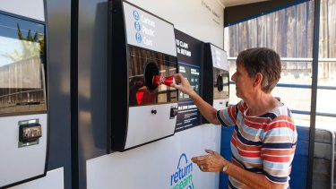 Una Bell loads a can into a Return and Earn reverse vending machine in Granville.