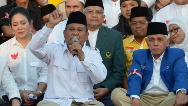 Defiant: presidential candidate Prabowo Subianto (with finger raised) is flanked by his ex-wife Hediati Suharto and running mate Hatta Rajasa at a rally earlier this week.