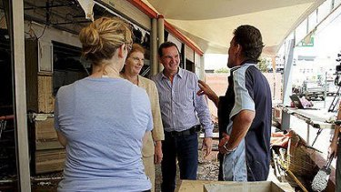 Queensland Governor Penelope Wensley and Ipswich Mayor Paul Pisasale manage to share a joke with the owners of Big Dad's Pies amongst the devastation caused by the floods.