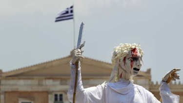 Jobs injustice ... performers from the French theatrical company Le Theatre du Soleil hold up a giant marionette of ''Justice'' with a bloodied face during a rally against austerity measures in Syntagma Square in central Athens.