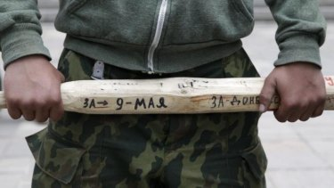A man holds a stick outside the regional government headquarters in Luhansk, eastern Ukraine.
