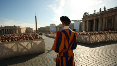 A Swiss Guard on patrol at the start of the General Audience with the Pope, attended by thousands of people in St Peter's Square at the Vatican.