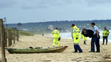 Police examine a kayak at Seaford Beach.