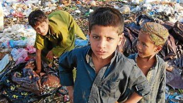 Afghan refugees search for scraps in a Pakistan refugee slum.
